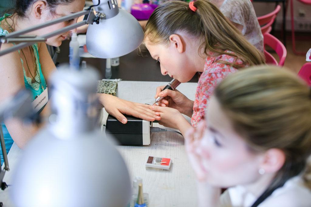Ученица отрабатывает навыки по аппаратному маникюру